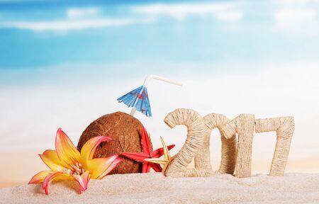 Sunny beach with an inscription 2017 Christmas coconut and starfish on sea background Standard-Bild - 142071727