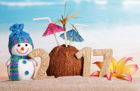 Christmas snowman, coconut with umbrellas and the inscription 2017 in the sand against the sea Standard-Bild - 142071754