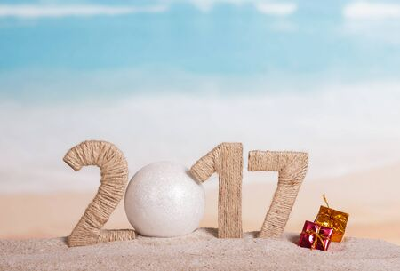 Christmas ball and the inscription 2017 in the sand against the sea Standard-Bild - 142072283