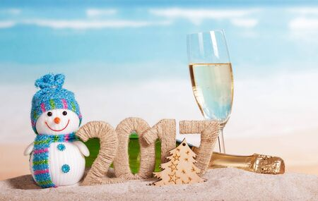 Christmas 2017 inscription, champagne, snowman in the sand on background of ocean Standard-Bild - 142072330