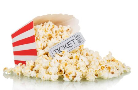 Popcorn spilled from a square box and gray movie ticket isolated on white background