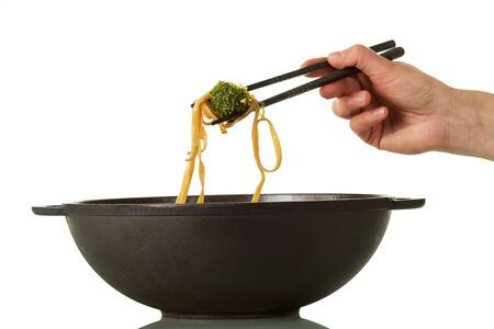 Female hand pulls from out frying pan wok portion of noodles with vegetables isolated on white background