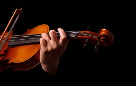 Violin in hands of musician isolated on black background