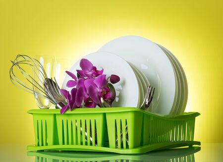 Clean plates, Cutlery and wine glasses, flowers on dryer, on yellow background
