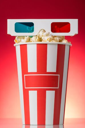 3D glasses in the box with popcorn on bright red background