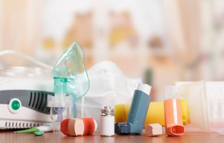 Compressor inhaler with child's mask and pocket device for asthmatics, on background of table