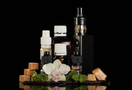 Electronic cigarette for smoking, set of liquids and aromatic oils, sweets, isolated on black background