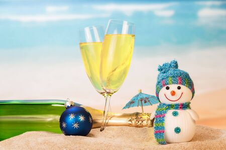 Bottle and two glasses with champagne, snowman, Christmas ball, umbrella in the sand against the sea. Stockfoto