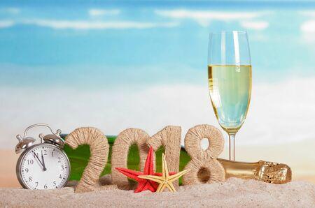 Neujahrsaufschrift 2018, eine Flasche und ein Glas Champagner, Uhr und Seestern auf dem Sand.