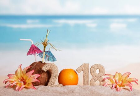 New Year inscription 2018, the orange instead of the numbers 0, coconut with straws and flowers in the sand. Standard-Bild - 142369602