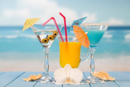 Cocktail, a glass of juice and alcohol with olives, umbrellas and straws, starfish, seashells and an orchid flower against the sea.