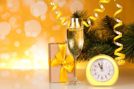 Champagne, spruce branch, box with gift on sparkling yellow background