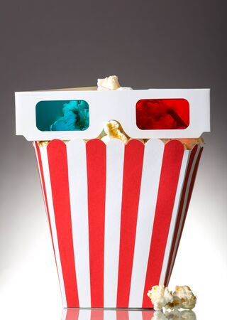 A large square box of popcorn and 3D glasses, several popcorn beside the gray background.