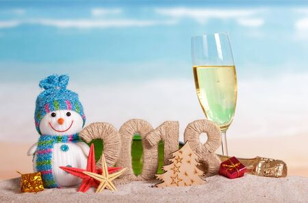 New Year inscription 2018, a bottle and a glass of champagne, snowman, gifts, starfish in the sand on the beach. Stock Photo