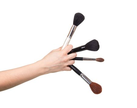 Four cosmetic brushes in a female hand isolated on a white background.