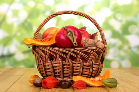 Basket with ripe apples, walnuts, slices of pumpkin and chestnuts near on an abstract green background. Zdjęcie Seryjne