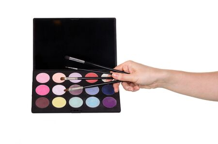 A palette of colorful eye shadow and make-up brushes isolated on a white background Stock Photo