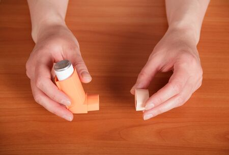 Female hands hold portable inhaler on background of table