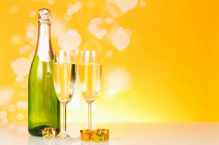 Bottle of champagne, wine glasses, small boxes with souvenirs on bright yellow background 写真素材 - 143268977