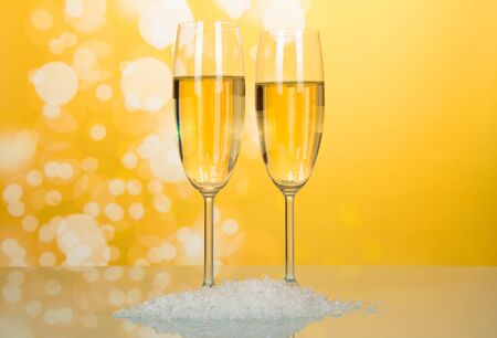 Two wonderful wineglass of champagne with bubbles of air, near handful of artificial snow on bright yellow background 写真素材 - 143273700