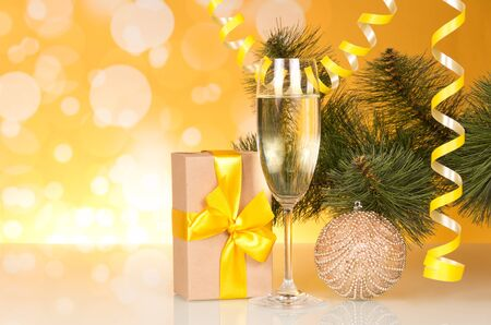 New year pine branches, streamer and toy, wine, gift, on bright yellow background