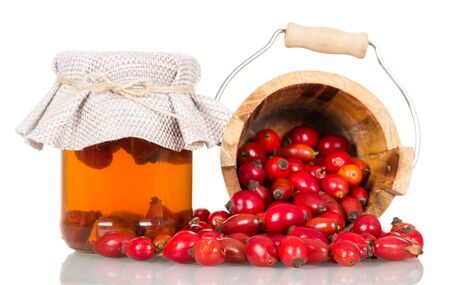 Broth briars in bank, berries crumbled out of wooden bucket isolated on white background
