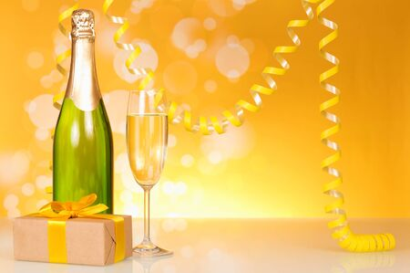 Bottle of champagne, glass of wine, gift in box, and serpentine, on bright yellow background 写真素材 - 143273890
