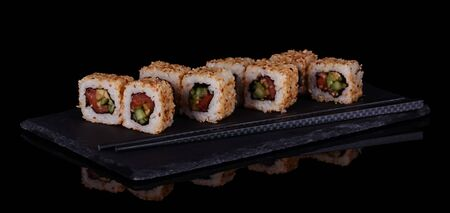 Sushi-rolls with seafood in sesame seeds on plate isolated on black background