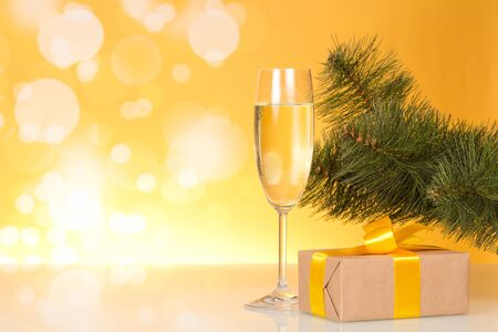 Christmas pine branch, glass of champagne and gift box with beautiful bow, on bright yellow background Stock fotó