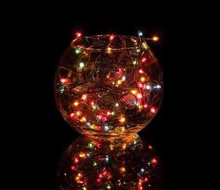 Multicolored lights of included garland glow in glass bowl isolated on black background