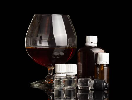 Glass with alcohol, set of liquids for smoking an electronic cigarette, isolated on black background