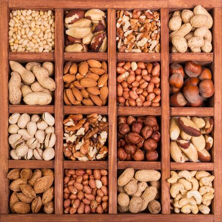 Large selection of peeled nuts, and kernels in shell, in wooden box with cells. Background
