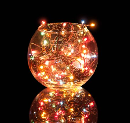 Sparkling Christmas garland is located in round glass shape isolated on black background