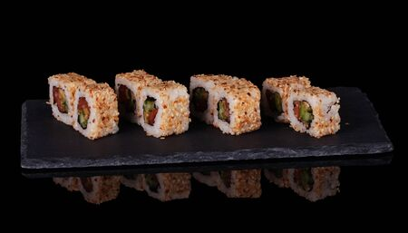 Traditional Asian platter of sushi on special stand, isolated on black background