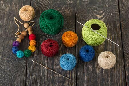 Balls of yarn in different colors and knitting hooks for craft on dark wooden surface