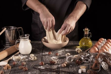 Hands Baker kneaded dough in bowl, isolated on black background