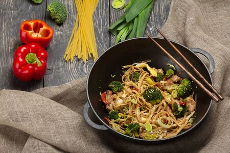 Traditional Asian dish, noodles with meat and vegetables in wok pan, chopsticks on burlap Imagens