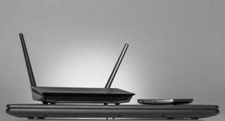 Modern digital technology-modem, computer, phone, on grey background