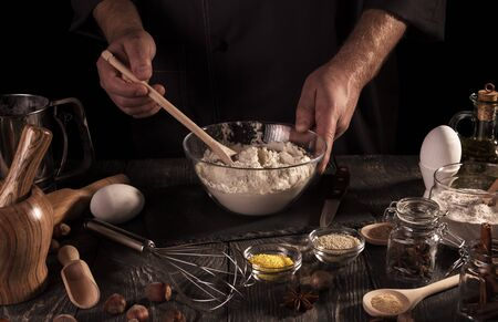 Hands Baker kneaded dough in glass bowl, isolated on black background Imagens