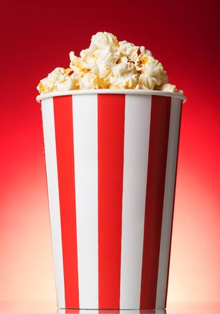 Striped box with popcorn on a red background