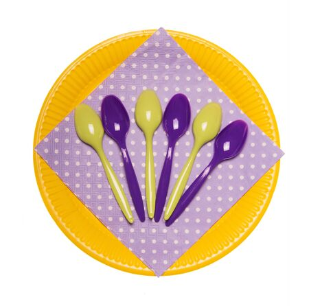 Colorful disposable plates, plastic spoons and doily isolated on a white background.