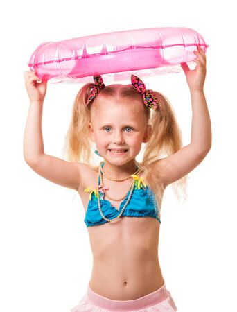 Little blond girl in a swimsuit holding an inflatable ring on the head isolated on white background.