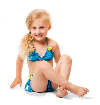Seated little blond girl in a swimsuit isolated on white background.