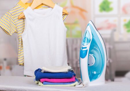 Steam iron, ironing board and clothes a children in the background of the room.