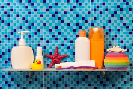 Shelf in a bathroom with the children's hygiene on abstract blue background. Archivio Fotografico
