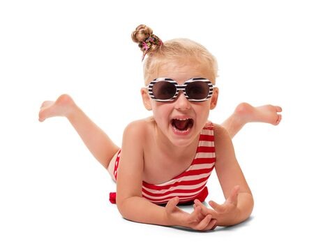 Reclining little blonde girl in swimsuit and sunglasses isolated on white background.