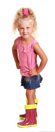 An impish little blond girl in a pink blouse and blue skirt, colorful rubber boots isolated on white background. Imagens
