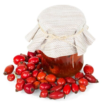 Rosehip berries and a glass jar with a drink isolated on white background. Standard-Bild
