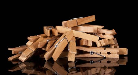 Pile of wooden clothespins isolated on a black background. Foto de archivo