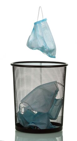Another medical mask flies into the bin, isolated on white background